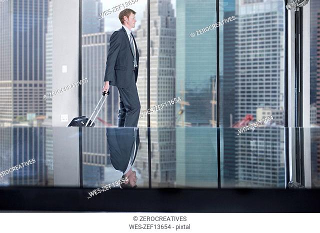 Businessman walking with rolling suitcase in city office