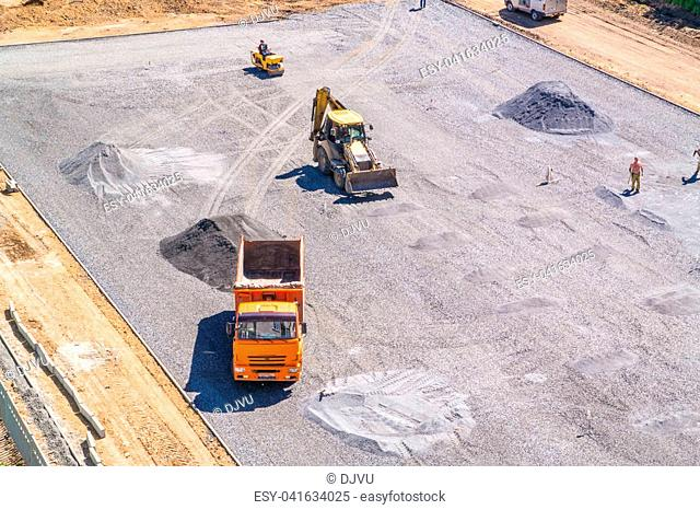 The construction of the school stadium. Excavator, dumper, roller