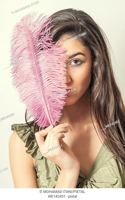 Young woman hiding face with a pink feather