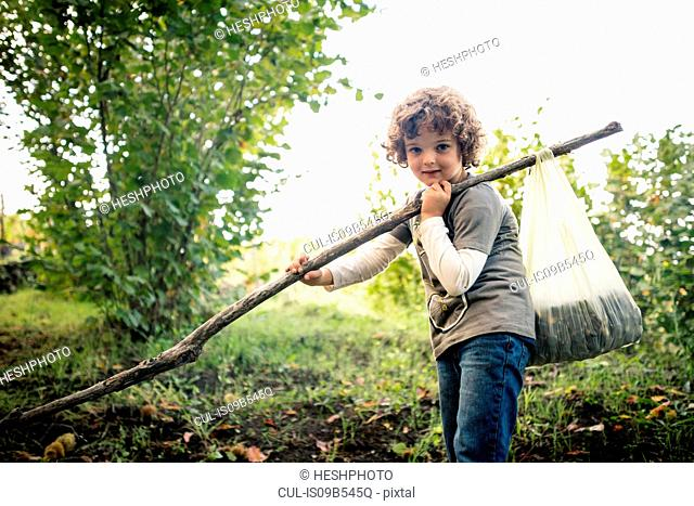 Portrait of boy with pole and chestnuts in vineyard woods
