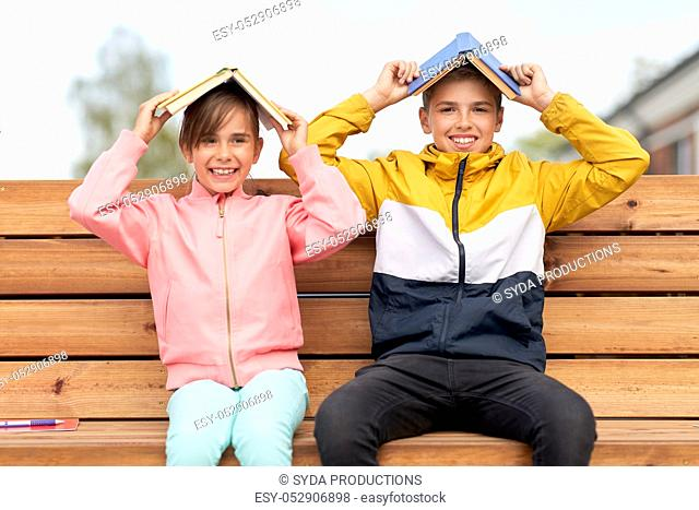 school children with books having fun outdoors