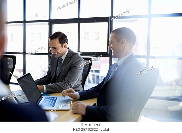 Businessmen smiling at laptop in conference room meeting