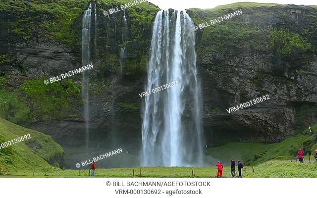 Iceland Seljalandsfoss Waterfalls famous water falls in South Iceland with 180 feet or 60 metres fall of water with tourists in bright colors