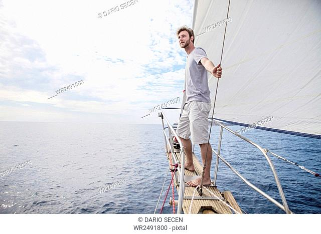 Man on bow of sailboat looking out over sea