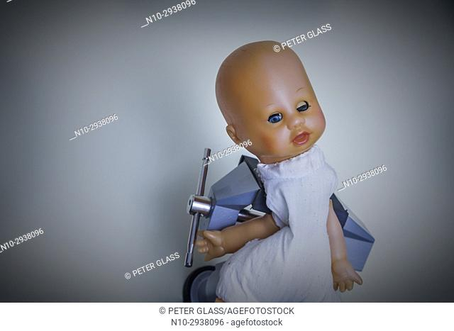 Baby doll being held tightly in a vise