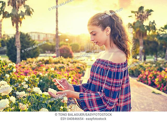 Girl portrait taking photos to a rose flower with smarphone
