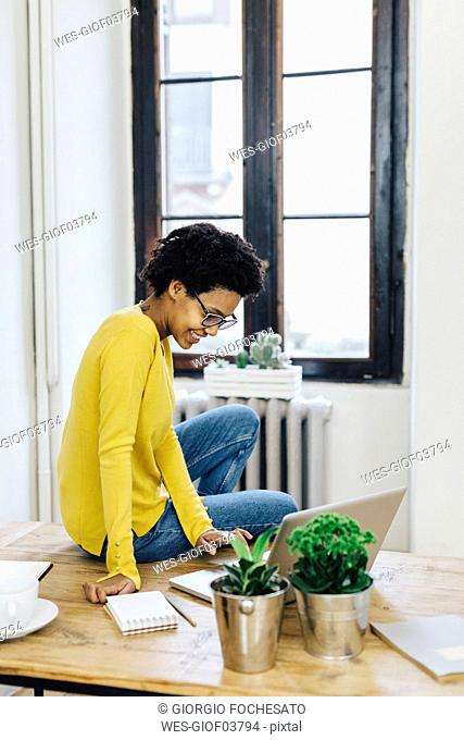 Young woman at home surfing the net, using laptop