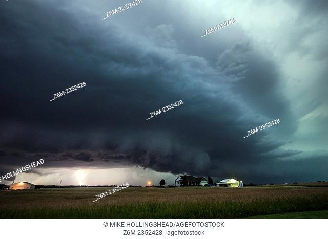Lightning strikes behind a shelf cloud in Kansas
