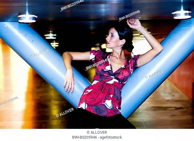 attractive blackhaired young woman leaning against a column