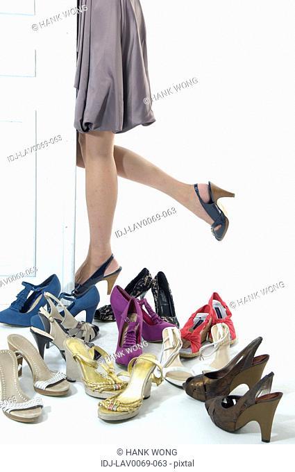 Woman standing beside a door near sandals