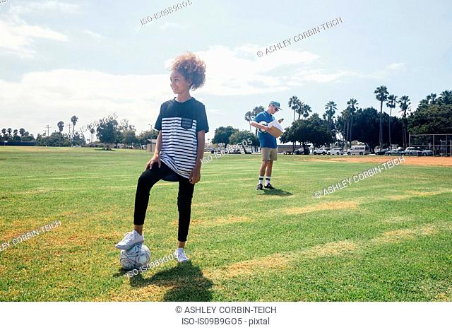 Portrait of schoolgirl with foot on soccer ball on school sports field