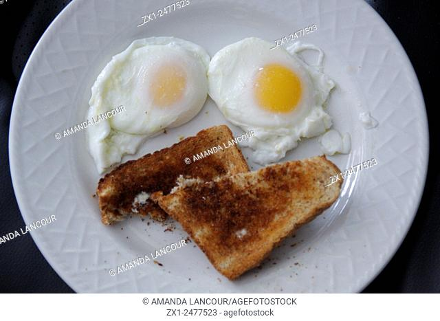 Eggs sunny-side up on a white plate with toast on a background. Heart healthy breakfast that looks like smiley face