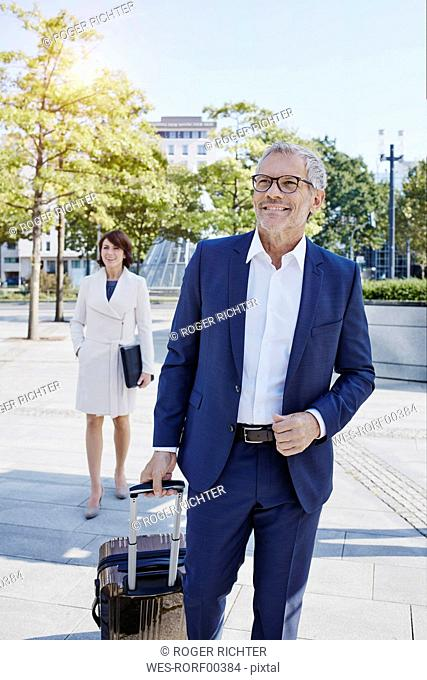 Smiling businessman on the go with businesswoman in background
