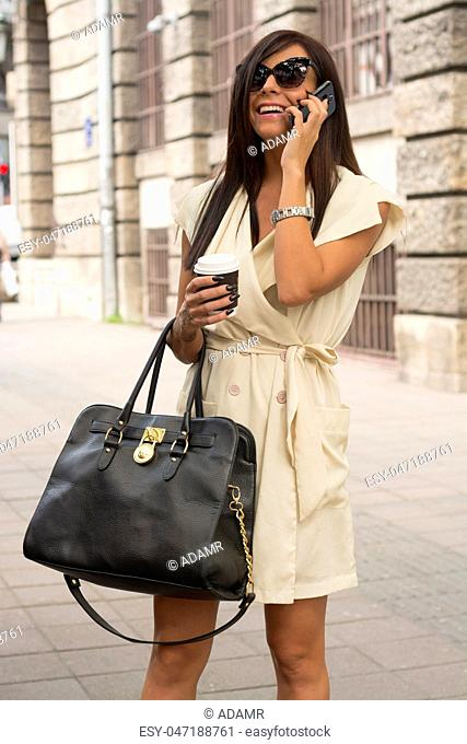 Stylish young business woman laughs into phone