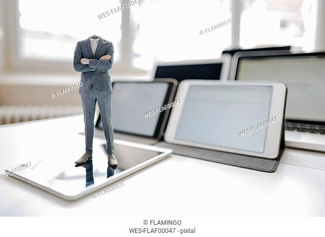 Headless businessman figurine standing on digital tablet on a desk