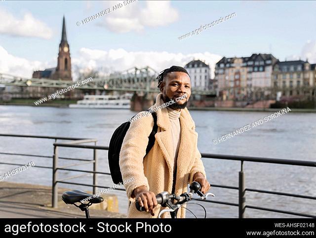 Portrait of stylish man with a bicycle walking on riverbank, Frankfurt, Germany