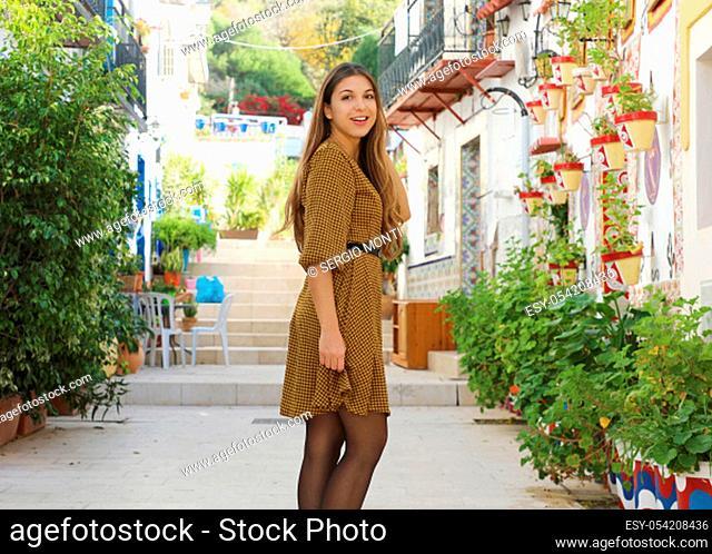 Young fashion woman walking in Santa Cruz old neighborhood of Alicante, Spain. Beautiful elegant girl visiting southern Europe