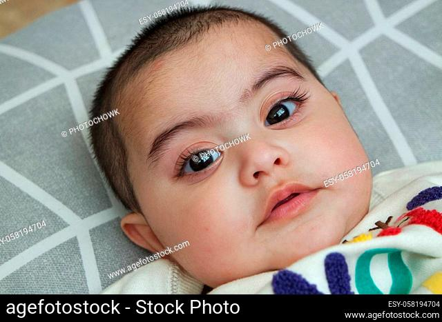 Baby girl with lovely face, big eyes and cute face gesture. Toddler baby making sweet activities