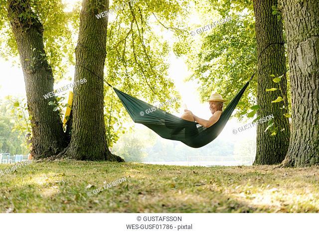 Senior man wearing straw hat relaxing in hammock at lakeshore reading book