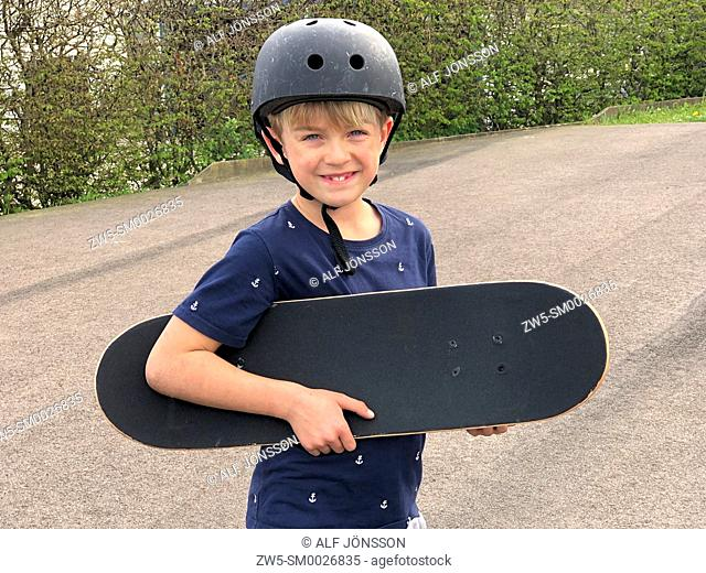 Boy, 9 years old; standing with a skateboard in Ystad, Scania, Sweden