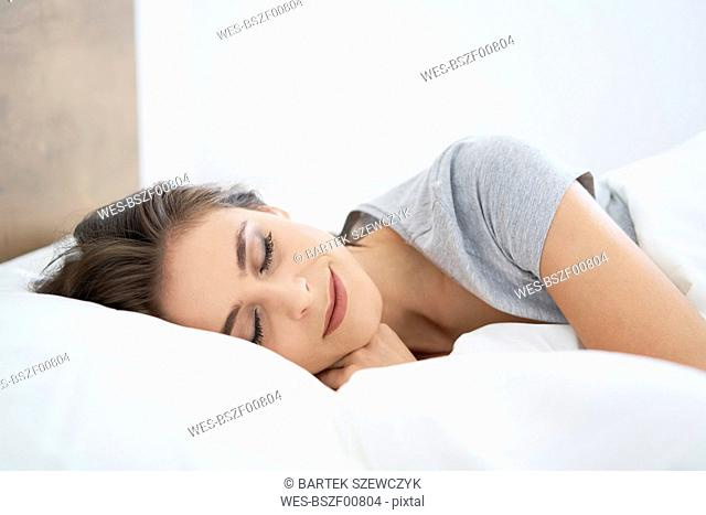 Young woman resting on bed, with eyes closed