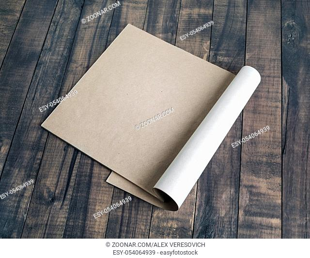 Blank booklet of kraft paper on wooden background