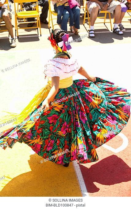 Hispanic girl in costume dancing