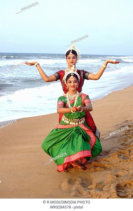 Dancers performing classical traditional odissi dance in front of bay of Bengal sea , Konarak , Orissa , India MR 736D,736C