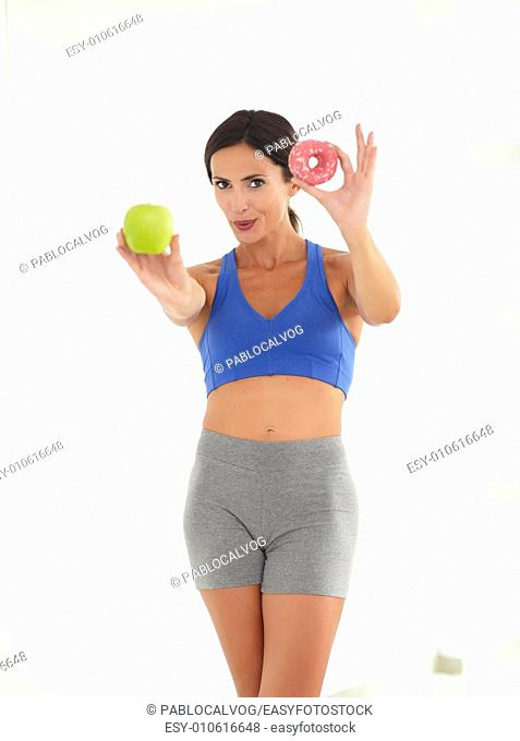 Fit female choosing between fruit and donut while looking at you