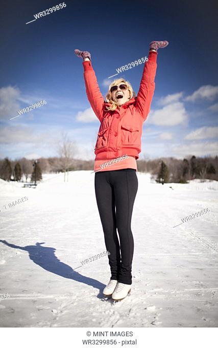 Caucasian woman on ice skates cheering on frozen lake