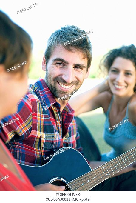 Young man playing guitar with friends