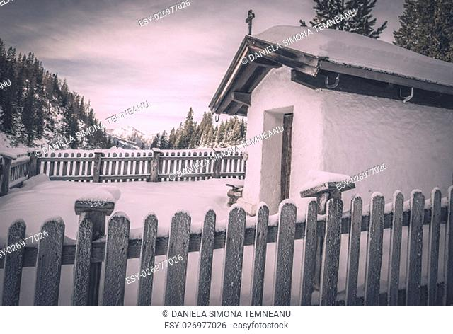 Winter scenery with a small, rustic chapel covered with snow, surrounded by a wooden fence and snowy trees. Image captured in Ehrwald, Austria