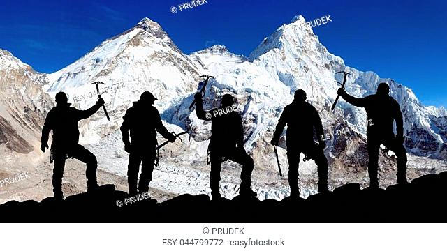 View of mount Everest and Lhotse from Pumo Ri base camp and silhouette of group of climbers with ice axe in hand, Everest area Khumbu valley