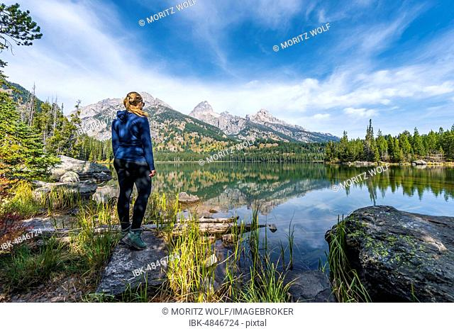 Young woman standing at a lake, reflection in Taggart Lake, view of the Teton Range mountain range, Grand Teton National Park, Wyoming, USA
