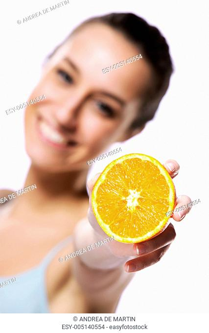 Beauty shot of a young woman with orange half on white backgroun