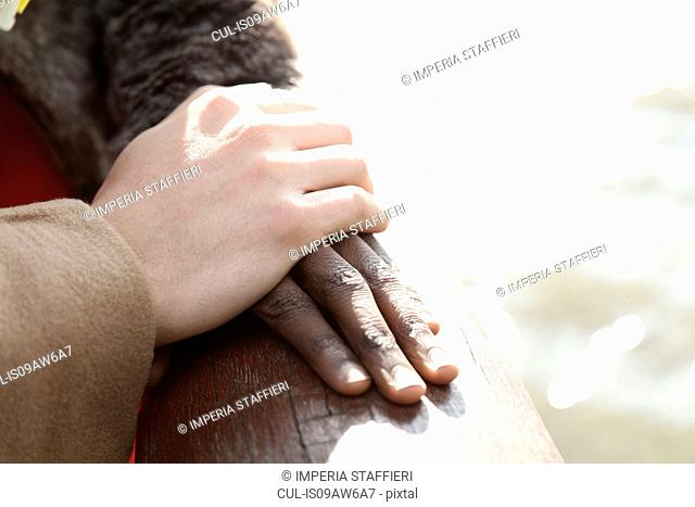 Multi ethnic couple outdoors, man resting hand on woman's hand, close-up