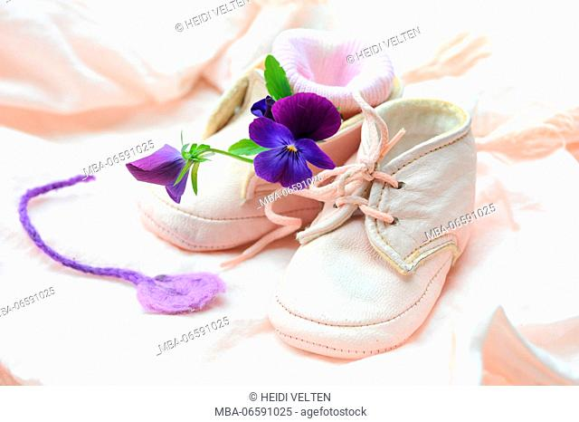Baby shoes, purple blossoms, still life