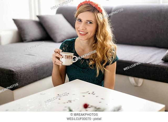Portrait of smiling young woman drinking coffee at home at Christmas time
