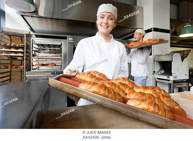 Smiling baker holding tray of bread in bakery kitchen