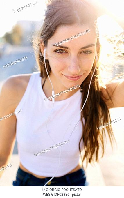Portrait of smiling young woman with earphones at sunset