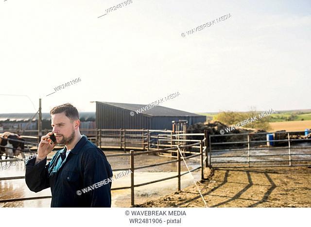 Farm worker talking on cellphone by fence