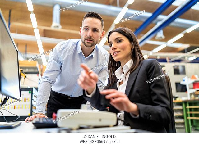 Businessman and businesswoman talking at computer in modern factory