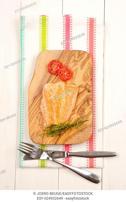 grilled salmon fillet with tomato and thyme on wooden board