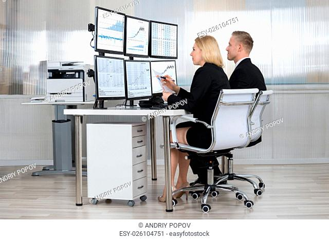 Financial workers analyzing data displayed on computer screens at desk in office