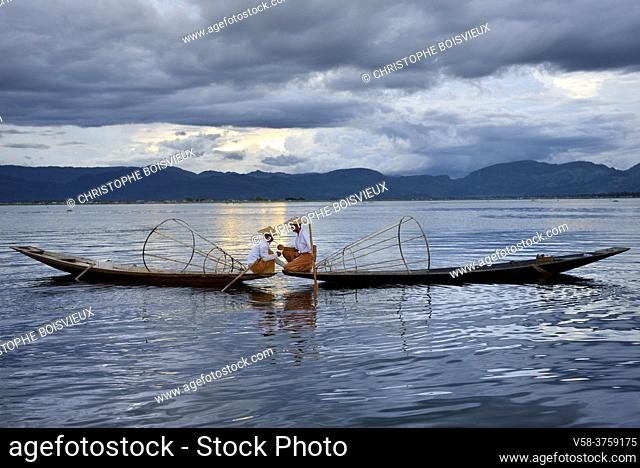 Myanmar, Shan State, Inle Lake, Intha fishermen lighting a cigar