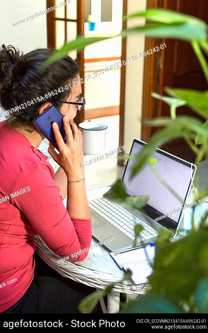 Woman working at home talking on the phone and drinking hot drink