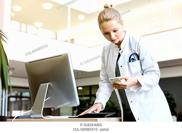 Doctor standing beside computer, holding open diary, looking at smartphone