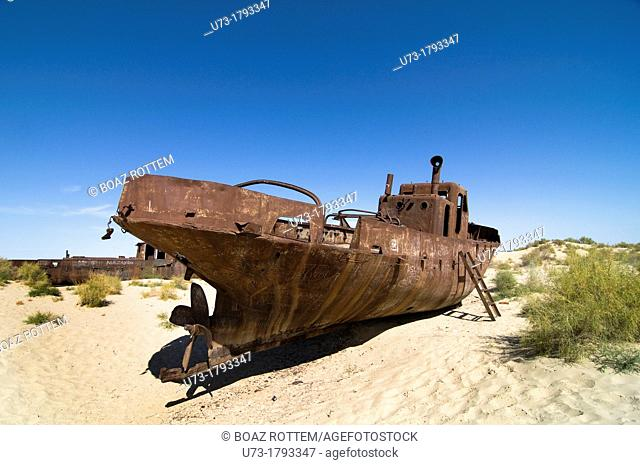 Rusty boats lay still on the dry desert sea bed of the dried Aral sea