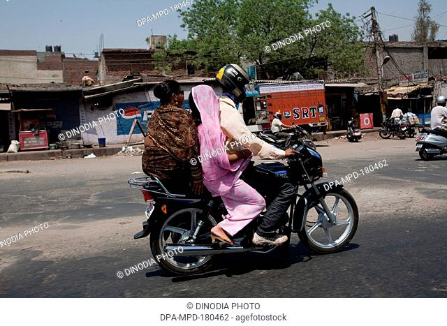 Passengers travelling motorbike on the streets New Delhi India Asia