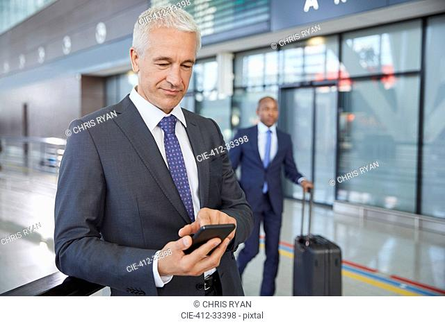 Businessman texting with cell phone in airport concourse